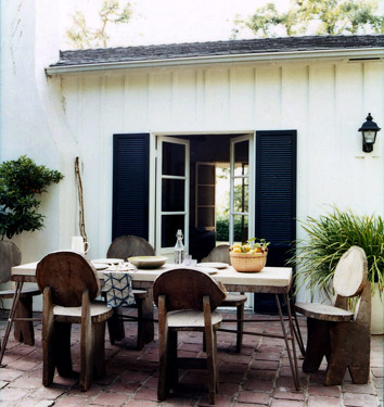 In the patio, rustic wood chairs are paired with a more modern table.