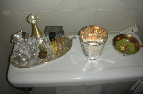 "On a silver serving dish, I arranged a mixture of antique and contemporary perfume bottles beside my votive and jewelry catch-all. Stay tuned for more changes like painting, a tub-side stool, and  some genuine original artwork not thrifted from my closets! Okay, I guess I didn't actually mean ""perfected,"" but I'm getting closer."