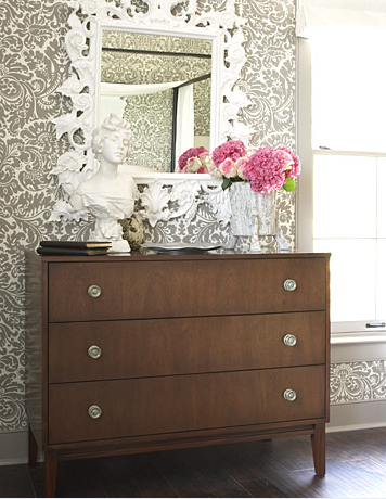 An ornate mirror works with this more modern and plain dresser.