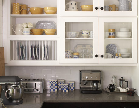 The kitchen's tech-savvy appliances are offset by the buttery richness of the yellow and blue tableware.