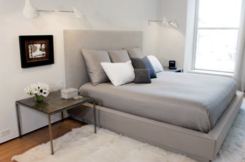 A bed dressed in cool, soothing grays encourages calm and sleep.