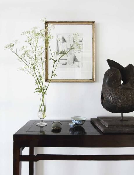 On a console table in the living room sits a Tibetan artifact, a small glass vase holding wild flowers, a small frame with a graphic drawing, and Delft bowls, which inspired the home's textiles.