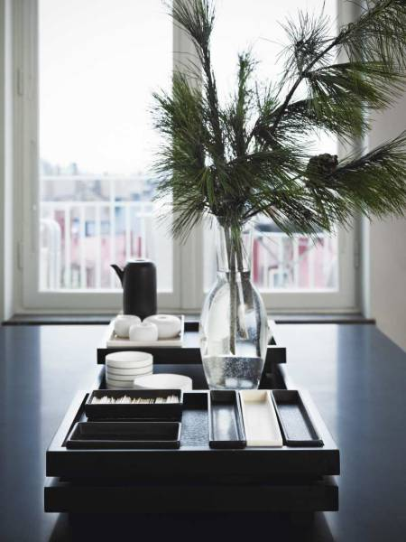 On the slick black coffee table in this all-white room is a collection of monochrome porcelain items and trays, alongside a vase filled with evergreen branches, which bring an organic element to the otherwise modern vignette.
