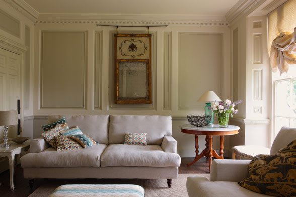Although its palette is reserved, this living room is given depth and interest by the decorative moldings.
