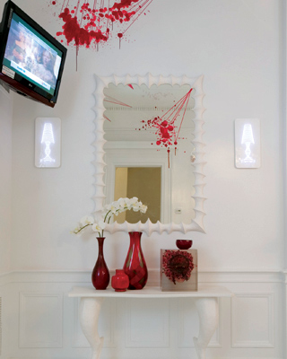 Spatters of red glass and resin art give this otherwise all-white vignette a punch of color.