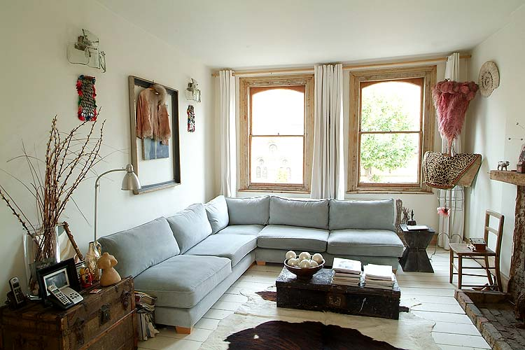 A super comfy pale blue sofa is the main attraction in this living room, and unique artifacts such as textiles and feather boas hung in an unusual manner give the room an eclectic, artsy style.