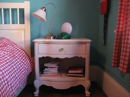 Upstairs, Laurel's bedroom is painted a cool turquoise blue, with red and pink accents. This little bedside table matches her dining room and living room pieces.