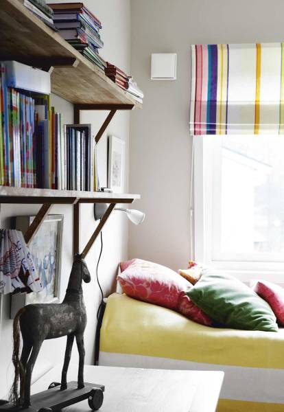 The guest room is cozy with an array of cheerful striped and solid textiles.