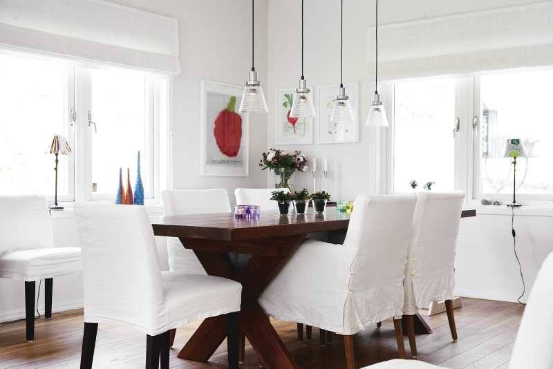 In the dining room, a trestle table is surrounded with simple white upholstered dining chairs, and pendants have glass shades, making the meal the main attraction.