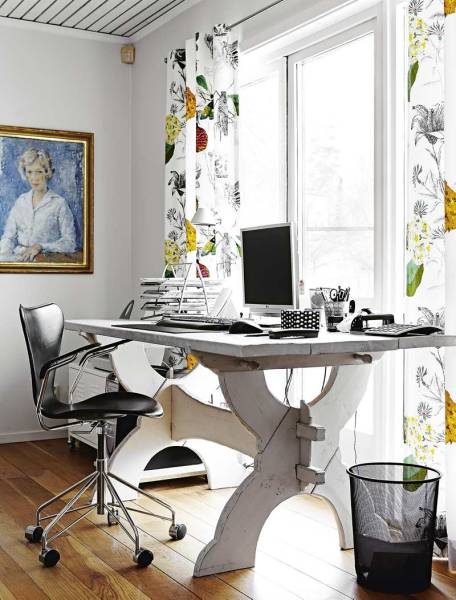 Patterned curtains and a family portrait brighten up this small home office.