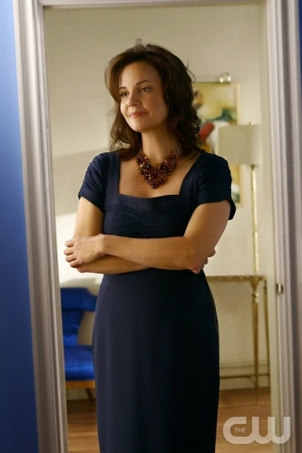 A bold blue slipper chair is a punch of color in Mrs. Waldorf's neutral room.