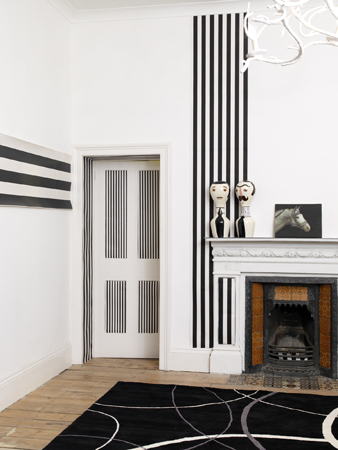 Bold black and white stripes and graphic patterns make this a clear departure from the rest of the house, but the artwork on the mantel has the same modern kitsch you see throughout.