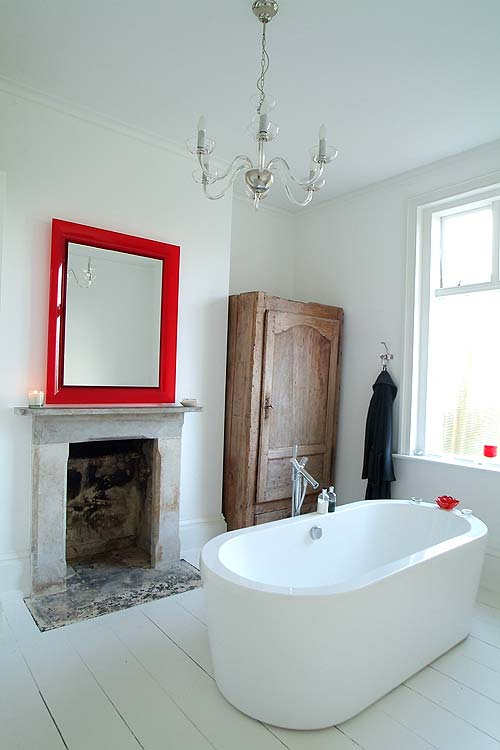 I love the juxtaposition of the worn-in hardwood floors and the modern tub, as well as how the small red dish picks up the color of the bold mirror. Wow.