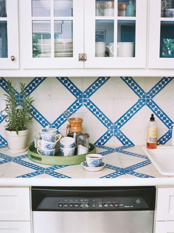 Who says you need to paint your walls a color? How about painting them white and then adding color with some hand-painted tiles on your back splash? Source