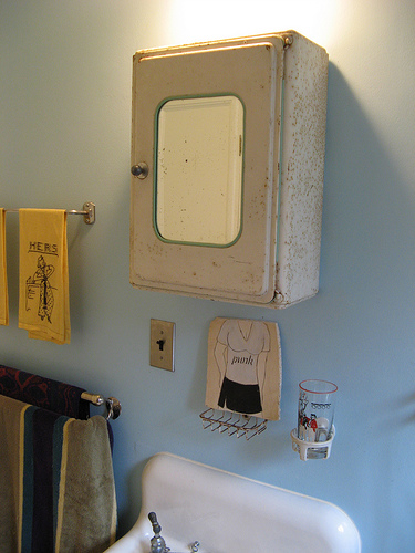 "Andy says, ""I removed the marble bathroom sink and replaced it with a cast iron one salvaged from my childhood home. The medicine cabinet is vintage tin from France."""