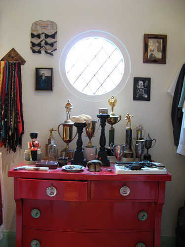 A bright red cabinet in the bedroom closet also supports vintage trophies. I love the bow tie collection, as well as the porthole window.
