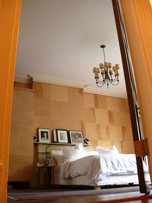 The bedroom walls are lined with squares of plywood for a quilted effect.