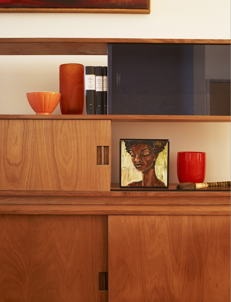 A warm wood console is given additional spark with red and orange accents and small artwork.
