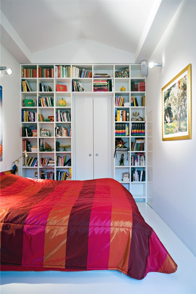 Wide and warm silk stripes are a powerful statement in this white bedroom. Columns and rows of books on the built-in mimic the graphic stripes.