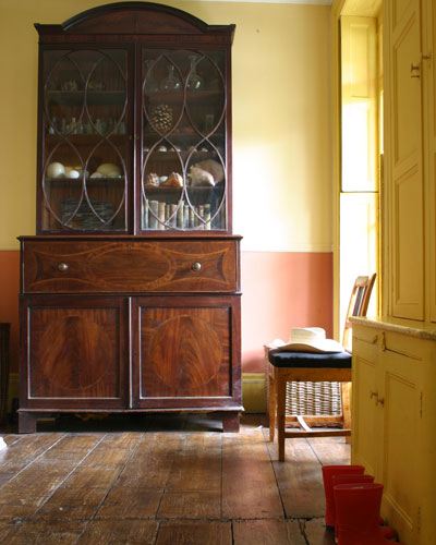 An antique wood-grain cabinet contrasts with the cheery, brightly painted yellow cupboard.