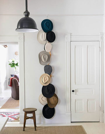 A vertical display of hats on a plain wall creates instant artwork.