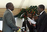 Zimbabwe's opposition leader Morgan Tsvangirai, head of the Movement for Democratic Change (MDC), is sworn in by President Rober
