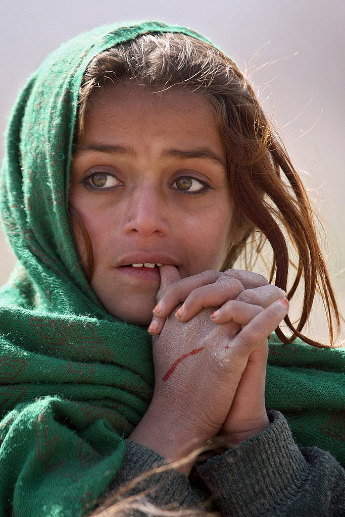 An Afghan girl waits in a line for distribution of food.