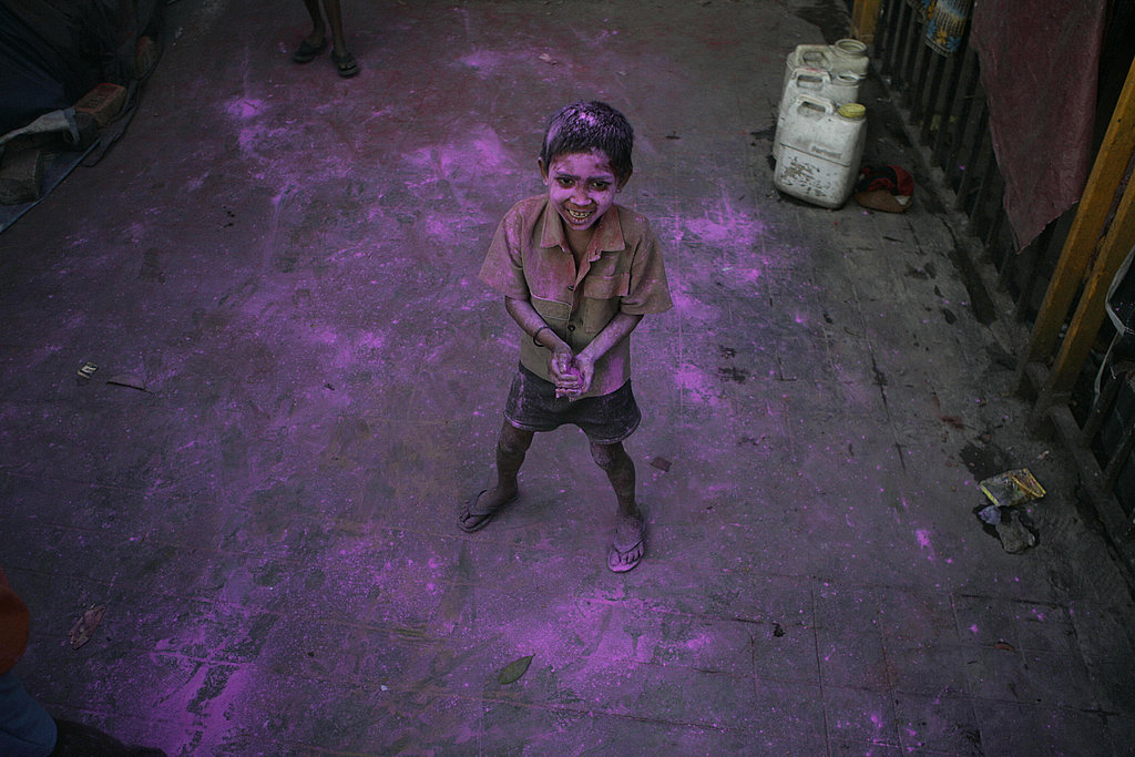 A boy waits with color dust to exchange with others in celebration.