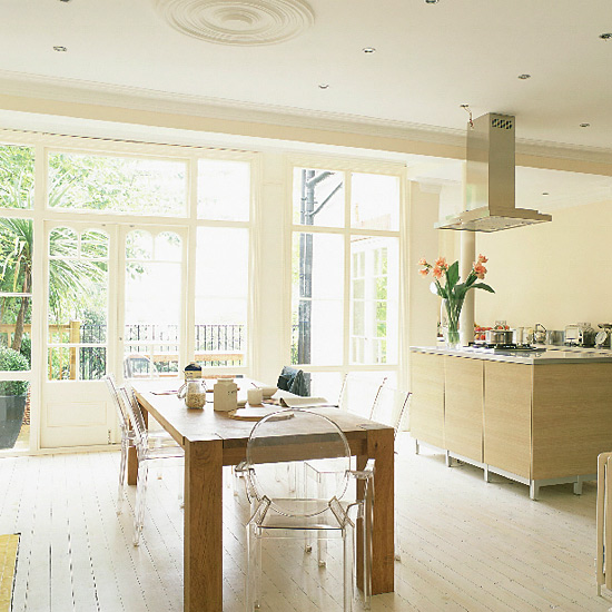 In this contemporary Victorian kitchen, a set of transparent Louis Ghost chairs allow the gorgeous natural light to take center stage. Source