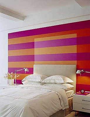 Thick and poppy painted stripes go undercover as a headboard in this bedroom. Source
