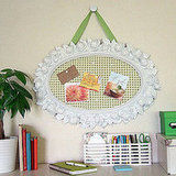 Crafty Nest turned an ugly plastic mirror into this pretty bulletin board.