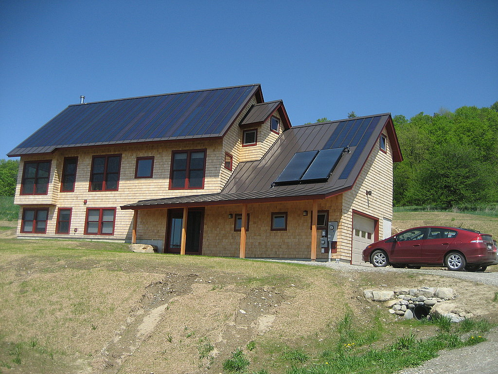 The house is a net-zero energy home, which means that the house is designed to produce as much energy as it uses. This is accomplished through energy efficiency and renewables. You can see the solar powers on the roof (they're the darker roof portions on the left hand side, and a small strip on the right).